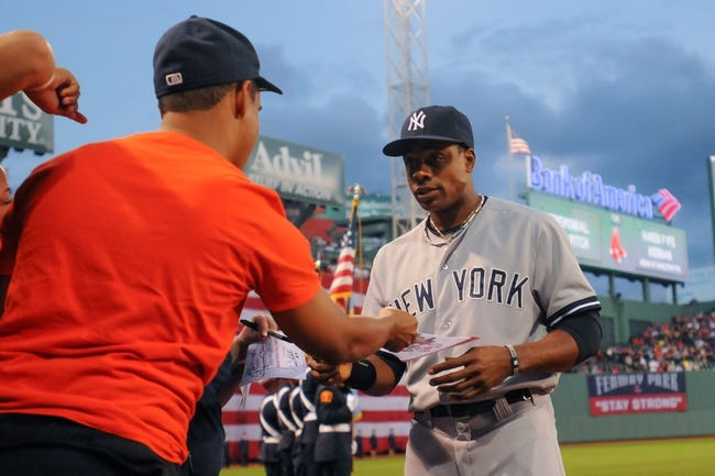 Sep 13, 2013; Boston, MA, USA; New York Yankees center fielder Curtis Granderson (14) signs an autograph prior to a game against the Boston Red Sox at Fenway Park. Mandatory Credit: Bob DeChiara-USA TODAY Sports