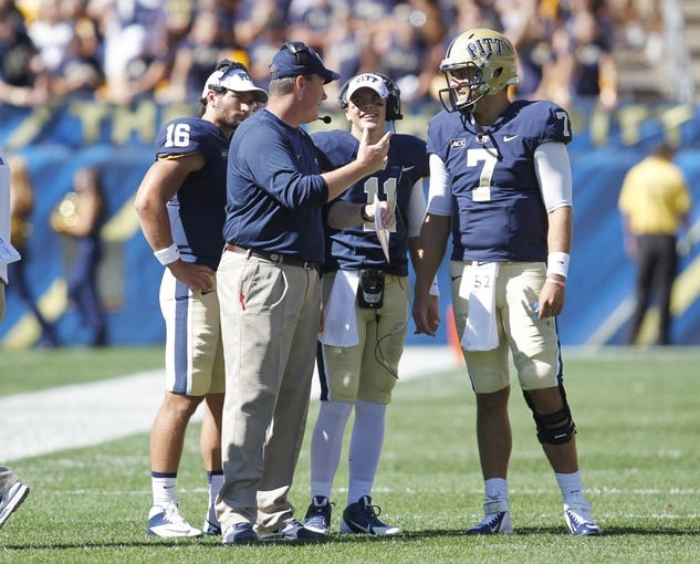 Sep 14, 2013; Pittsburgh, PA, USA; Pittsburgh Panthers head coach Paul Chryst ( center left) talks with quarterbacks Chad Voytik (16) and Trey Anderson (11) and Tom Savage (7) during a time-out against the New Mexico Lobos during the fourth quarter at Heinz Field. The Pittsburgh Panthers won 49-27. Mandatory Credit: Charles LeClaire-USA TODAY Sports