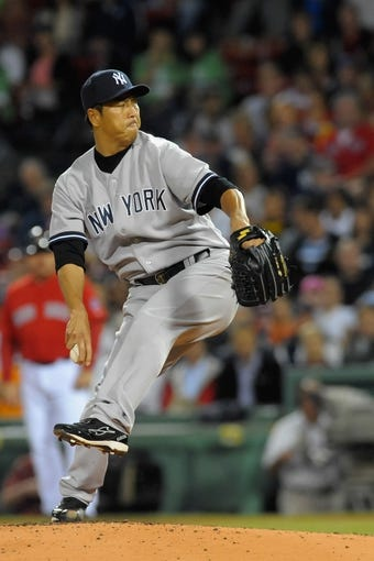 Sep 13, 2013; Boston, MA, USA; New York Yankees starting pitcher Hiroki Kuroda (18) pitches during the first inning against the Boston Red Sox at Fenway Park. Mandatory Credit: Bob DeChiara-USA TODAY Sports