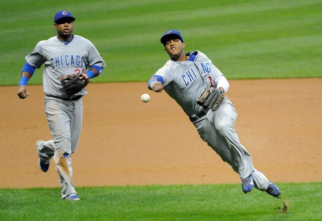 Sep 16, 2013; Milwaukee, WI, USA;  Chicago Cubs shortstop Starlin Castro (right) throws out Milwaukee Brewers shortstop Jean Segura (not pictured) as third baseman Luis Valbuena (left) watches in the first inning at Miller Park. Mandatory Credit: Benny Sieu-USA TODAY Sports