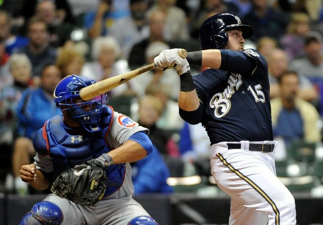 Sep 16, 2013; Milwaukee, WI, USA;  Milwaukee Brewers left fielder Caleb Gindl (right) hits a triple to drive in a run in the fourth inning as Chicago Cubs catcher Welington Castillo (left) watches at Miller Park. Mandatory Credit: Benny Sieu-USA TODAY Sports