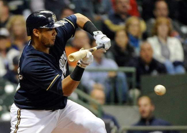 Sep 16, 2013; Milwaukee, WI, USA; Milwaukee Brewers catcher Martin Maldonado drops down a bunt to squeeze in a run in the fourth inning during the game against the Chicago Cubs at Miller Park. Mandatory Credit: Benny Sieu-USA TODAY Sports