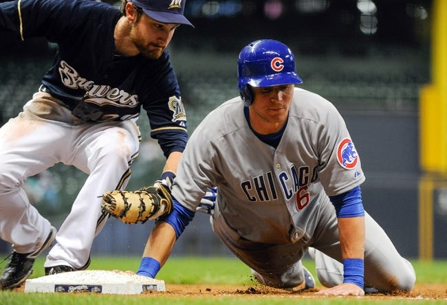 Sep 16, 2013; Milwaukee, WI, USA;  Chicago Cubs center fielder Ryan Sweeney (right) gets back to first base before tag by Milwaukee Brewers first baseman Jonathan Lucroy (left) on a pickoff attempt in the sixth inning at Miller Park. Mandatory Credit: Benny Sieu-USA TODAY Sports