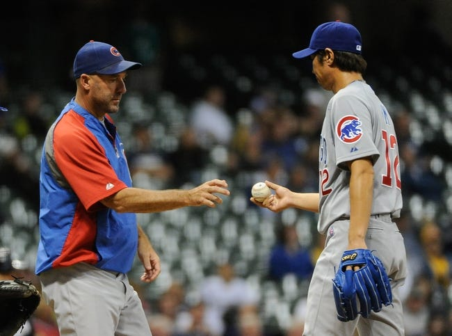 Sep 16, 2013; Milwaukee, WI, USA;  Chicago Cubs manager Dale Sveum (left) takes the ball from pitcher Chang-Yong Lim as he makes a pitching change in the seventh inning during the game against the Milwaukee Brewers at Miller Park. Mandatory Credit: Benny Sieu-USA TODAY Sports
