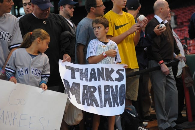 Sep 15, 2013; Boston, MA, USA; A fan holds a sign in honor of New York Yankees relief pitcher Mariano Rivera (not pictured) who is retiring at the end of the season prior to a game against the Boston Red Sox at Fenway Park. Mandatory Credit: Bob DeChiara-USA TODAY Sports