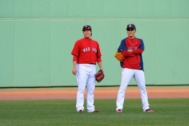 Sep 15, 2013; Boston, MA, USA; Boston Red Sox relief pitcher Junichi Tazawa (36) and closer Koji Uehara (19) in the outfield during batting practice prior to a game against the New York Yankees at Fenway Park. Mandatory Credit: Bob DeChiara-USA TODAY Sports