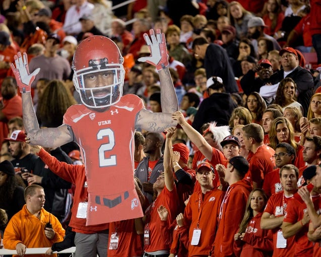 Sep 14, 2013; Salt Lake City, UT, USA; Utah Utes fans hold up a cardboard cutout of injured wide receiver Kenneth Scott (2) during the second half against the Oregon State Beavers at Rice-Eccles Stadium. Oregon State won 51-48 in overtime. Mandatory Credit: Russ Isabella-USA TODAY Sports