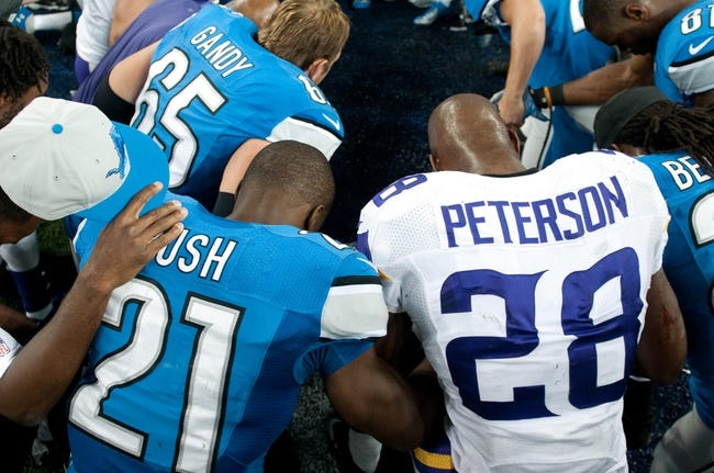 Sep 8, 2013; Detroit, MI, USA;  Detroit Lions running back Reggie Bush (21) and Minnesota Vikings running back Adrian Peterson (28) pray after the game against at Ford Field. Detroit won 34-24. Mandatory Credit: Tim Fuller-USA TODAY Sports