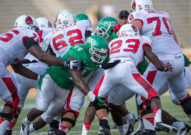 Sep 14, 2013; Denton, TX, USA; North Texas Mean Green defensive end Aaron Bellazin (44) tackles Ball State Cardinals running back Teddy Williamson (23) during the game at Apogee Stadium. The Mean Green defeated the Cardinals 34-27. Mandatory Credit: Jerome Miron-USA TODAY Sports