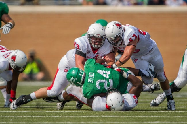 Sep 14, 2013; Denton, TX, USA; Ball State Cardinals defensive tackle Joel Cox (93) and linebacker Zack Ryan (53) tackle North Texas Mean Green running back Brandin Byrd (24) during the game at Apogee Stadium. The Mean Green defeated the Cardinals 34-27. Mandatory Credit: Jerome Miron-USA TODAY Sports