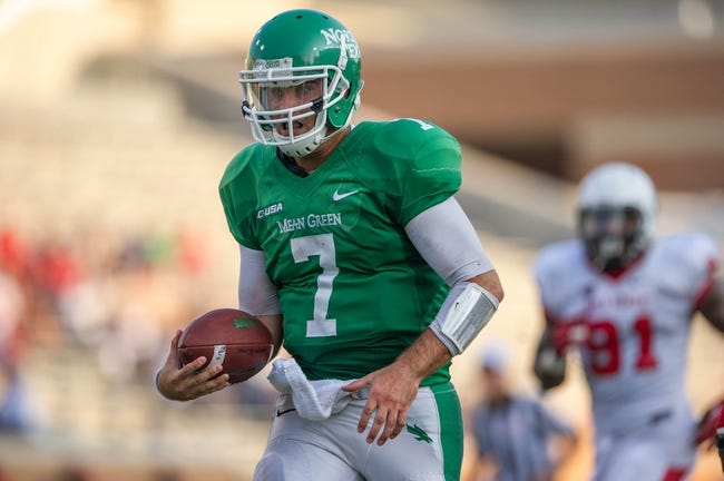 Sep 14, 2013; Denton, TX, USA; North Texas Mean Green quarterback Derek Thompson (7) runs for a touchdown during the game against the Ball State Cardinals at Apogee Stadium. The Mean Green defeated the Cardinals 34-27. Mandatory Credit: Jerome Miron-USA TODAY Sports