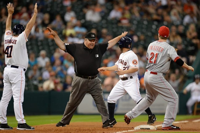 Sep 17, 2013; Houston, TX, USA; Umpire Wally Bell (35) calls Houston Astros second baseman Jose Altuve (27) safe against Cincinnati Reds third baseman Todd Frazier (21) during the first inning at Minute Maid Park. Mandatory Credit: Thomas Campbell-USA TODAY Sports