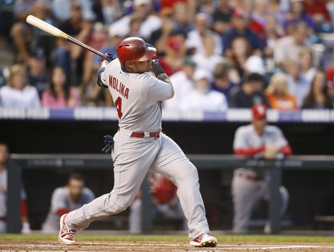 Sep 17, 2013; Denver, CO, USA; St. Louis Cardinals catcher Yadier Molina (4) hits an RBI single during the first inning against the Colorado Rockies at Coors Field. Mandatory Credit: Chris Humphreys-USA TODAY Sports