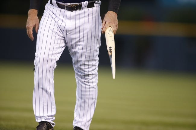 Sep 17, 2013; Denver, CO, USA; Colorado Rockies first base coach Rene Lachemann (38) carries a piece of a broken bat from left fielder Corey Dickerson (not pictured) during the first inning against the St. Louis Cardinals at Coors Field. Mandatory Credit: Chris Humphreys-USA TODAY Sports