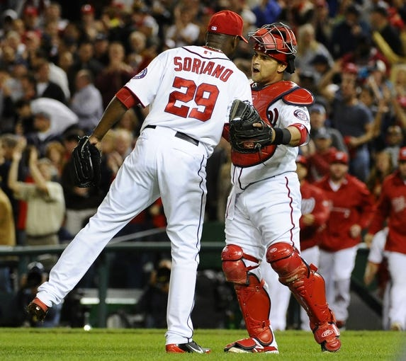 Sep 17, 2013; Washington, DC, USA; Washington Nationals relief pitcher Rafael Soriano (29) is congratulated by catcher Jhonatan Solano (23) after recording the final out against the Atlanta Braves at Nationals Park. The Nationals won 4-0. Mandatory Credit: Brad Mills-USA TODAY Sports