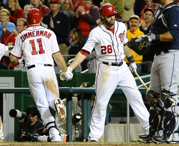 Sep 17, 2013; Washington, DC, USA; Washington Nationals third baseman Ryan Zimmerman (11) is congratulated by right fielder Jayson Werth (28) after hitting a solo home during the eighth inning against the Atlanta Braves at Nationals Park. The Nationals won 4-0. Mandatory Credit: Brad Mills-USA TODAY Sports