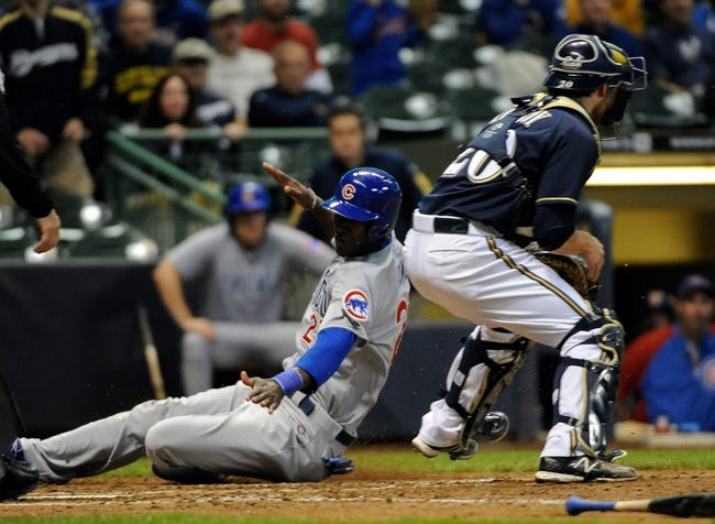 Sep 17, 2013; Milwaukee, WI, USA;   Chicago Cubs left fielder Junior Lake (left) scores past Milwaukee Brewers catcher Jonathan Lucroy in the seventh inning at Miller Park. Mandatory Credit: Benny Sieu-USA TODAY Sports