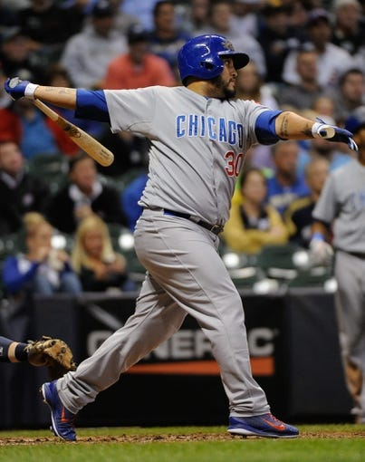 Sep 17, 2013; Milwaukee, WI, USA; Chicago Cubs catcher Dioner Navarro hits a double in the eighth inning against the Milwaukee Brewers at Miller Park. Mandatory Credit: Benny Sieu-USA TODAY Sports