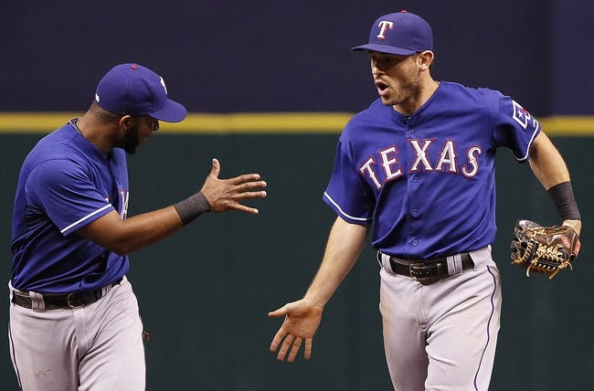 Sep 17, 2013; St. Petersburg, FL, USA; Texas Rangers second baseman Ian Kinsler (5) celebrates with shortstop Elvis Andrus (1) after Kinsler made the last out in the eighth inning against the Tampa Bay Rays at Tropicana Field. The Rangers won 7-1. Mandatory Credit: Kim Klement-USA TODAY Sports