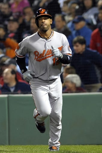 Sep 17, 2013; Boston, MA, USA; Baltimore Orioles pinch runner Alexi Casilla (12) scores on a sacrifice fly during the ninth inning against the Boston Red Sox at Fenway Park. Mandatory Credit: Bob DeChiara-USA TODAY Sports