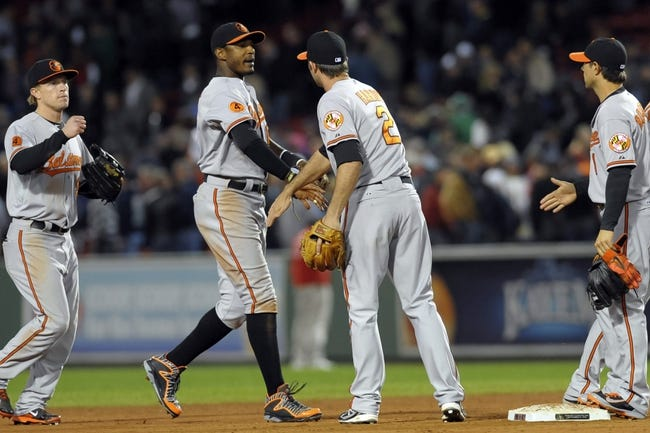 Sep 17, 2013; Boston, MA, USA; Baltimore Orioles shortstop J.J. Hardy (2) (middle) congratulates center fielder Adam Jones (10) after defeating the Boston Red Sox at Fenway Park. Mandatory Credit: Bob DeChiara-USA TODAY Sports