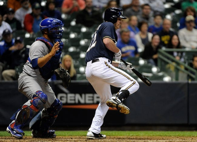 Sep 17, 2013; Milwaukee, WI, USA;   Milwaukee Brewers left fielder Logan Schafer puts down a bunt to squeeze in the winning run in the ninth inning as Chicago Cubs catcher Welington Castillo watches at Miller Park. Mandatory Credit: Benny Sieu-USA TODAY Sports