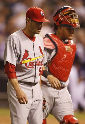 Sep 17, 2013; Denver, CO, USA; St. Louis Cardinals starting pitcher Joe Kelly (58) and catcher Yadier Molina (4) return to the dugout during the fifth inning against the Colorado Rockies at Coors Field. Mandatory Credit: Chris Humphreys-USA TODAY Sports