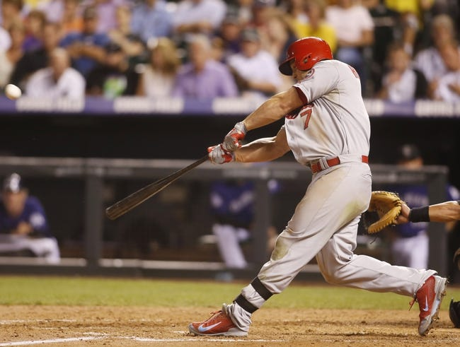 Sep 17, 2013; Denver, CO, USA; St. Louis Cardinals left fielder Matt Holiday (7) hits a home run during the fifth inning against the Colorado Rockies at Coors Field. Mandatory Credit: Chris Humphreys-USA TODAY Sports