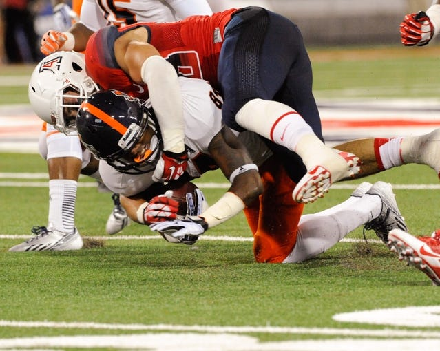 Sep 14, 2013; Tucson, AZ, USA; Arizona Wildcats safety Jared Tevis (38) tackles Texas-San Antonio Roadrunners wide receiver Brandon Freeman (84) during the third quarter at Arizona Stadium. The Wildcats defeated the Roadrunners 38-13. Mandatory Credit: Casey Sapio-USA TODAY Sports