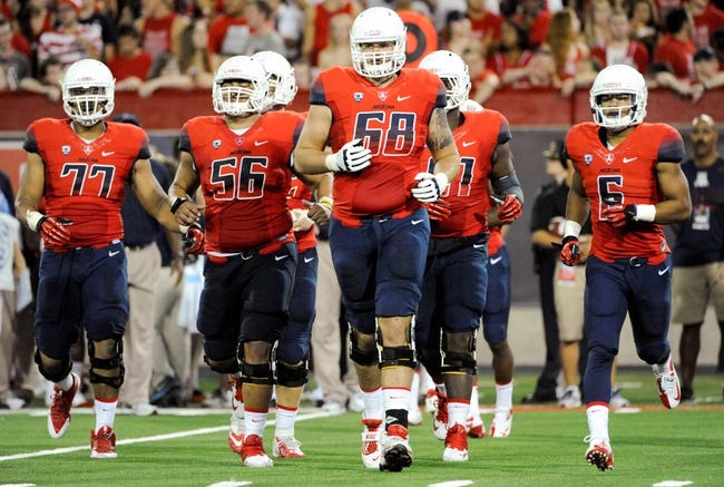 Sep 14, 2013; Tucson, AZ, USA; Arizona Wildcats offensive lineman Lene Maiava (77) offensive lineman Steven Gurrola (56) offensive lineman Mickey Baucus (68) and receiver Nate Phillips (6) run on to the field during the second quarter against the Texas-San Antonio Roadrunners at Arizona Stadium. The Wildcats defeated the Roadrunners 38-13. Mandatory Credit: Casey Sapio-USA TODAY Sports