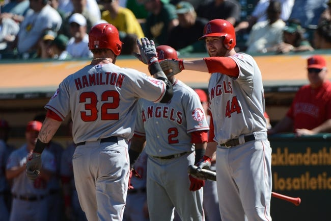 September 18, 2013; Oakland, CA, USA; Los Angeles Angels designated hitter Josh Hamilton (32) is congratulated by shortstop Erick Aybar (2) and first baseman Mark Trumbo (44) after hitting a two-run home run against the Oakland Athletics during the ninth inning at O.co Coliseum. The Angels defeated the Athletics 5-4 in 11 innings. Mandatory Credit: Kyle Terada-USA TODAY Sports