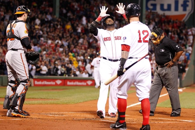 Sep 18, 2013; Boston, MA, USA; Boston Red Sox designated hitter David Ortiz (34) hits a two-run home run against the Baltimore Orioles in the first inning at Fenway Park. Mandatory Credit: David Butler II-USA TODAY Sports