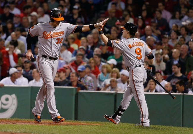 Sep 18, 2013; Boston, MA, USA; Baltimore Orioles catcher Matt Wieters (32) is congratulated by left fielder Nate McLouth (9) after scoring against the Boston Red Sox in the fifth inning at Fenway Park. Mandatory Credit: David Butler II-USA TODAY Sports