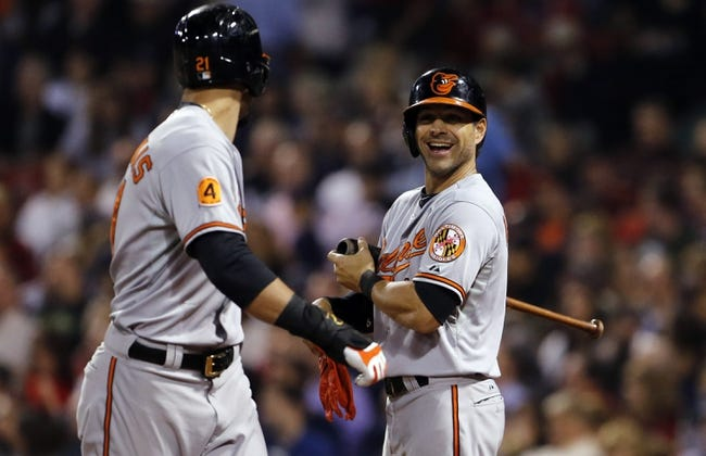 Sep 18, 2013; Boston, MA, USA; Baltimore Orioles second baseman Brian Roberts (1) congratulates right fielder Nick Markakis (21) after scoring the go ahead run against the Boston Red Sox in the sixth inning at Fenway Park. Mandatory Credit: David Butler II-USA TODAY Sports