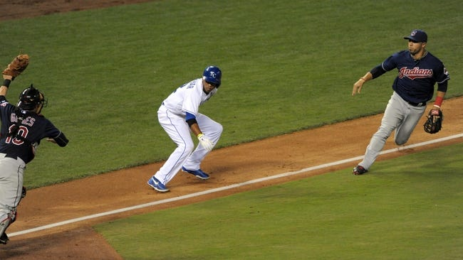 Sep 18, 2013; Kansas City, MO, USA; Kansas City Royals shortstop Alcides Escobar (2) is caught in a run down between Cleveland Indians catcher Yan Gomes (10) and shortstop Mike Aviles (4) in the fifth inning at Kauffman Stadium. Mandatory Credit: Denny Medley-USA TODAY Sports