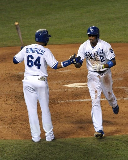 Sep 18, 2013; Kansas City, MO, USA; Kansas City Royals shortstop Alcides Escobar (2) is congratulated by second baseman Emilio Bonifacio (64) after Escobar scores a run in the fifth inning of the game against the Cleveland Indians at Kauffman Stadium. Mandatory Credit: Denny Medley-USA TODAY Sports