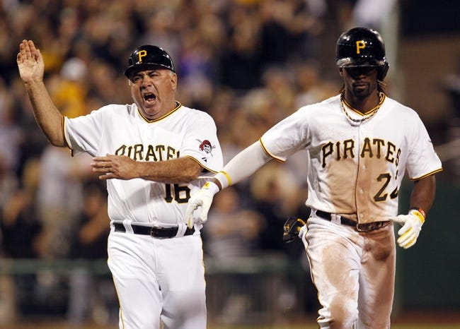 Sep 18, 2013; Pittsburgh, PA, USA; Pittsburgh Pirates third base coach Nick Leyva (16) reacts with center fielder Andrew McCutchen (22) after McCutchen hit a two run home run against the San Diego Padres during the seventh inning at PNC Park. The San Diego Padres won 3-2. Mandatory Credit: Charles LeClaire-USA TODAY Sports