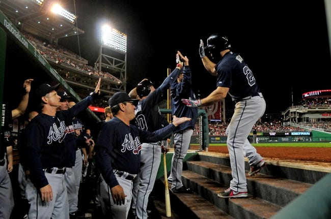 Sep 18, 2013; Washington, DC, USA; Atlanta Braves second baseman Dan Uggla (right) is congratulated by teammates after hitting a solo home run in the sixth inning against the Washington Nationals at Nationals Park. Mandatory Credit: Evan Habeeb-USA TODAY Sports