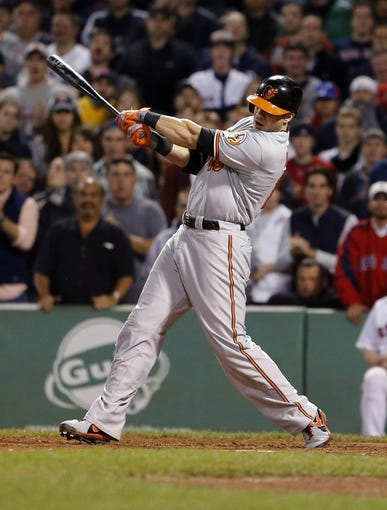 Sep 18, 2013; Boston, MA, USA; Baltimore Orioles first baseman Chris Davis (19) hits a single to drive in two runs in the twelfth inning against the Boston Red Sox at Fenway Park. Mandatory Credit: David Butler II-USA TODAY Sports