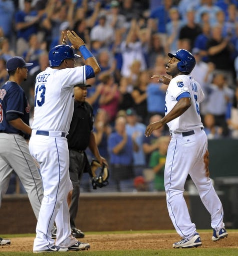 Sep 18, 2013; Kansas City, MO, USA; Kansas City Royals center fielder Lorenzo Cain (6) is congratulated by catcher Salvador Perez (13) after Cain scores in the eighth inning of the game against the Cleveland Indians at Kauffman Stadium. The Royals won 7-2. Mandatory Credit: Denny Medley-USA TODAY Sports