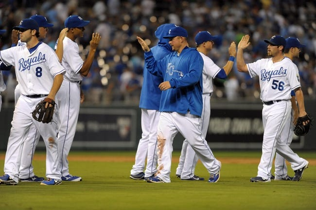 Sep 18, 2013; Kansas City, MO, USA; Kansas City Royals third baseman Mike Moustakas (8), designated hitter Billy Butler (16) and relief pitcher Greg Holland (56) are congratulated by teammates after the game against the Cleveland Indians at Kauffman Stadium. The Royals won 7-2. Mandatory Credit: Denny Medley-USA TODAY Sports