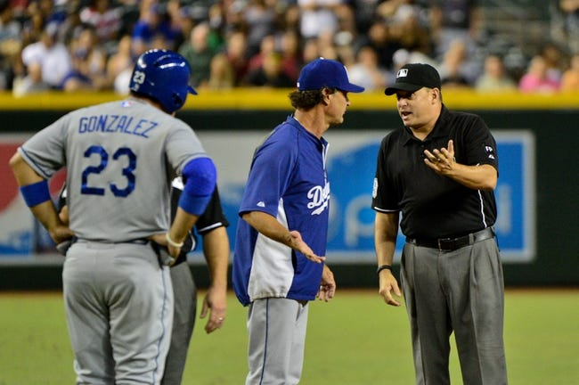 Sep 18, 2013; Phoenix, AZ, USA; Los Angeles Dodgers manager Don Mattingly (8) talks with MLB umpire Andy Fletcher as first baseman Adrian Gonzalez (23) looks on during the sixth inning against the Arizona Diamondbacks at Chase Field. Mandatory Credit: Matt Kartozian-USA TODAY Sports