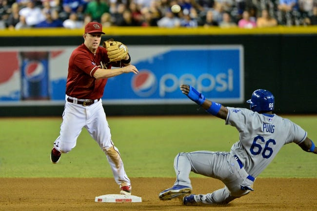 Sep 18, 2013; Phoenix, AZ, USA; Arizona Diamondbacks second baseman Aaron Hill (2) turns a double play as Los Angeles Dodgers right fielder Yasiel Puig (66) slides during the seventh inning at Chase Field. Mandatory Credit: Matt Kartozian-USA TODAY Sports