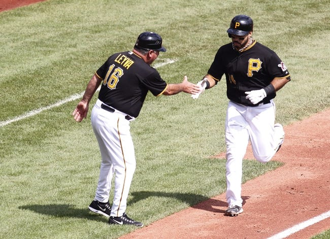 Sep 19, 2013; Pittsburgh, PA, USA; Pittsburgh Pirates third base coach Nick Leyva (16) greets third baseman Pedro Alvarez (24) after Alvarez hit a solo home run against the San Diego Padres during the fourth inning at PNC Park. Mandatory Credit: Charles LeClaire-USA TODAY Sports