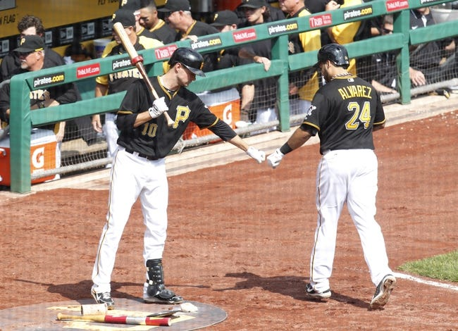 Sep 19, 2013; Pittsburgh, PA, USA; Pittsburgh Pirates shortstop Jordy Mercer (10) greets third baseman Pedro Alvarez (24) after Alvarez hit a solo home run against the San Diego Padres during the fourth inning at PNC Park. Mandatory Credit: Charles LeClaire-USA TODAY Sports