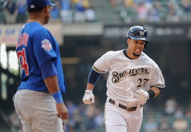 Sep 19, 2013; Milwaukee, WI, USA;   Milwaukee Brewers center fielder Carlos Gomez (right) runs the bases past Chicago Cubs third baseman Luis Valbuena (left) after hitting a solo homer in the seventh inning at Miller Park. Mandatory Credit: Benny Sieu-USA TODAY Sports