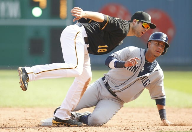 Sep 19, 2013; Pittsburgh, PA, USA; Pittsburgh Pirates second baseman Neil Walker (18) and San Diego Padres shortstop Ronny Cedeno (3) look for the umpires call after a close play at second base during the ninth inning against at PNC Park. Cedeno was ruled safe on the play. The Pittsburgh Pirates won 10-1. Mandatory Credit: Charles LeClaire-USA TODAY Sports