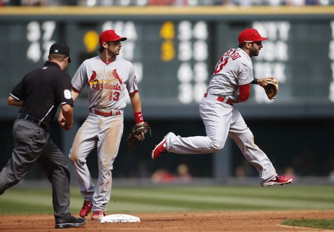 Sep 19, 2013; Denver, CO, USA; St. Louis Cardinals shortstop Daniel Descalso (33) turns a double play during the second inning against the Colorado Rockies at Coors Field. Mandatory Credit: Chris Humphreys-USA TODAY Sports