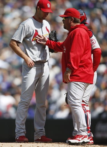 Sep 19, 2013; Denver, CO, USA; St. Louis Cardinals pitching coach Derek Lilliquist (center) talks with starting pitcher Michael Wacha (left) during the second inning against the Colorado Rockies at Coors Field. Mandatory Credit: Chris Humphreys-USA TODAY Sports