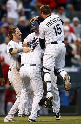 Sep 19, 2013; Denver, CO, USA; Members of the Colorado Rockies celebrate with center fielder Corey Dickerson after he hit a walk off triple to win the game during the fifthteenth inning against the St. Louis Cardinals  at Coors Field. The Rockies won 7-6 in 15 innings.  Mandatory Credit: Chris Humphreys-USA TODAY Sports